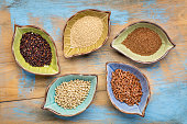a set of five gluten free grains (sorghum, teff, amaranth,brown rice and quinoa) - top view of leaf shape bowl against grunge, painted wood