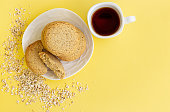 Gluten free homemade oats oatmeal cookies and cup tea or coffee espresso on pastel yellow background. Top view. Copy space.