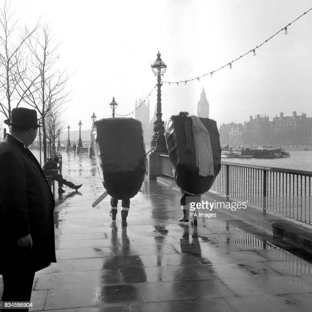 Glyn Elias and his cousin Raymond Rees from Carmarthenshire in Wales carrying their coracles to a launching off the Festival Hall Pier London They...