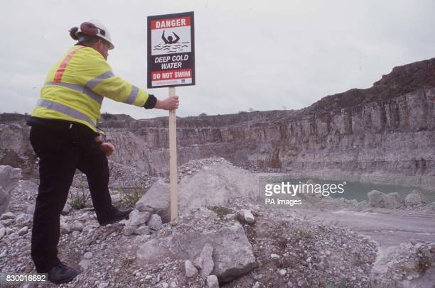 Glyn Williams one of Tarmac's Health Safety and Environment Advisors putting up a safety sing at Middle Peak Quarry in Matlock Derbyshire The sing is...