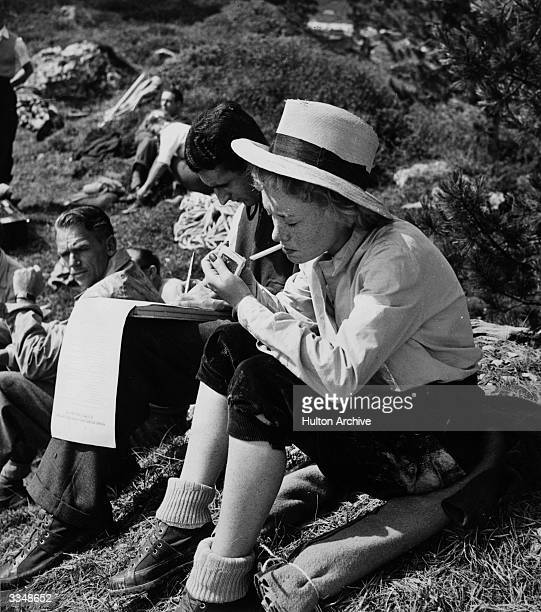 Glynis Johns lights a cigarette while relaxing between scenes on location filming 'State Secret' in the Dolomites