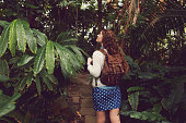 Young caucasian woman with a backpack on her shoulders exploring the wild nature.
