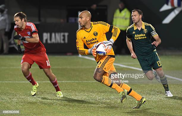 Goal keeper Adam Kwarasey of Portland Timbers runs with the ball as Ryan Hollingshead of FC Dallas and Jack Jewsbury of Portland Timbers close in...