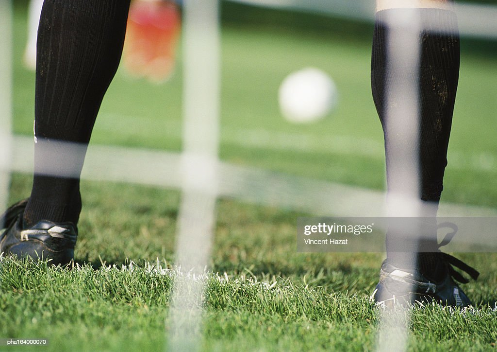 Goal keeper in front of goal area, low section, blurred. : Stock Photo