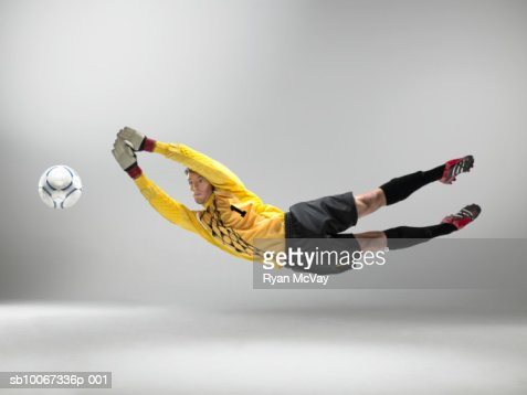Goal keeper jumping to catch football (studio shot)