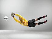Goal keeper jumping to catch football (studio shot)