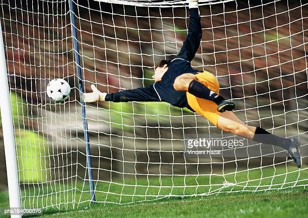 Goal keeper reaching for soccer ball.
