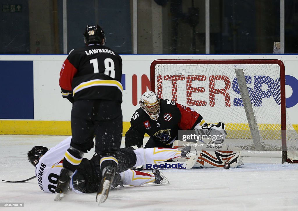 Goal tender Martins Raitums of Nottingham Panthers save a shot on goal by Lars Bryggman #38 of Lulea during the Champions Hockey League group stage game between Nottingham Panthers and Lulea Hockeyat at the National Ice Centre on August 24, 2014 in Nottingham, England.