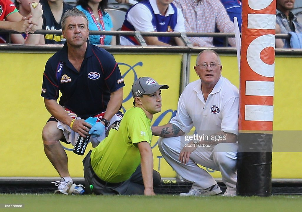 Goal umpire Courtney Lai lies on the ground waiting for assistance after injuring his knee after he was struck by Liam Picken of the Bulldogs during the round two AFL match between the Western Bulldogs and the Fremantle Dockers at Etihad Stadium on April 6, 2013 in Melbourne, Australia.