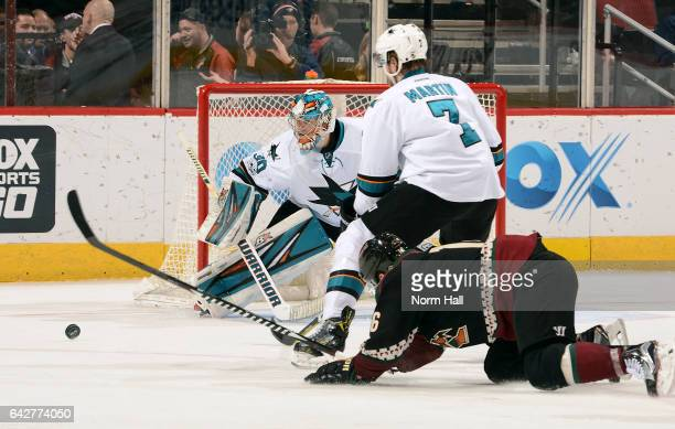 Goalie Aaron Dell of the San Jose Sharks keeps his eye on the puck as Paul Martin of the Sharks knocks it away from Max Domi of the Arizona Coyotes...
