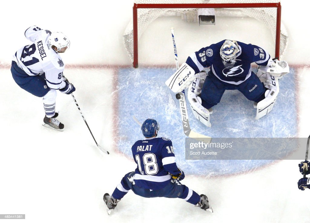 Goalie <a gi-track='captionPersonalityLinkClicked' href=/galleries/search?phrase=Anders+Lindback&family=editorial&specificpeople=7211274 ng-click='$event.stopPropagation()'>Anders Lindback</a> #39 of the Tampa Bay Lightning bats the puck away while teammate Ondrej Palat #18 and <a gi-track='captionPersonalityLinkClicked' href=/galleries/search?phrase=Phil+Kessel&family=editorial&specificpeople=537794 ng-click='$event.stopPropagation()'>Phil Kessel</a> #81 of the Toronto Maple Leafs look for a rebound during the first period at the Tampa Bay Times Forum on April 8, 2014 in Tampa, Florida.