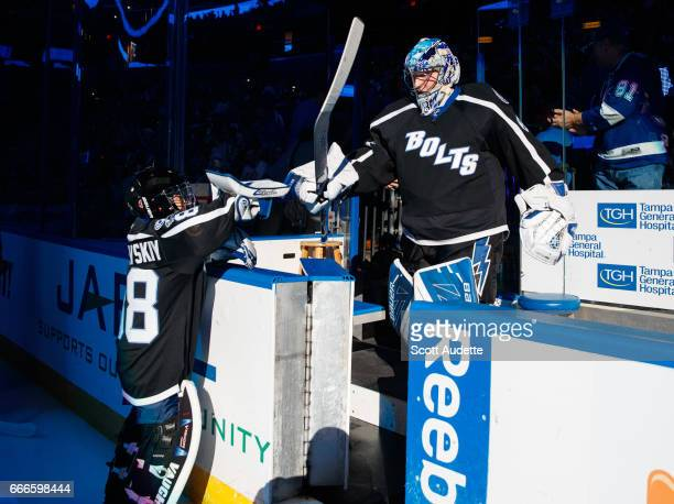 Goalie Andrei Vasilevskiy of the Tampa Bay Lightning bumps blockers with the Thunder Kid before the game against the Buffalo Sabres at Amalie Arena...