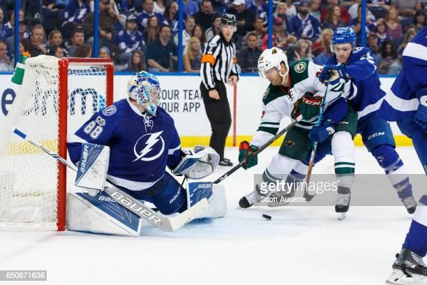 Goalie Andrei Vasilevskiy of the Tampa Bay Lightning makes a save as teammate Brayden Point battles against Jason Pominville of the Minnesota Wild...