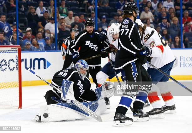 Goalie Andrei Vasilevskiy of the Tampa Bay Lightning makes a save as teammates Nikita Kucherov and Victor Hedman battle against Aleksander Barkov and...