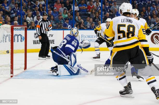 Goalie Andrei Vasilevskiy of the Tampa Bay Lightning misses stopping the puck and gives up a goal against the Pittsburgh Penguins during the second...