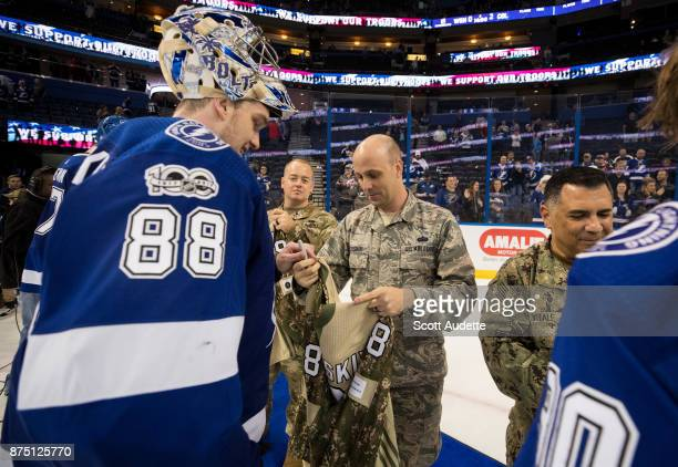 Goalie Andrei Vasilevskiy of the Tampa Bay Lightning signs a jersey for a member of the military after the win against the Dallas Stars at Amalie...