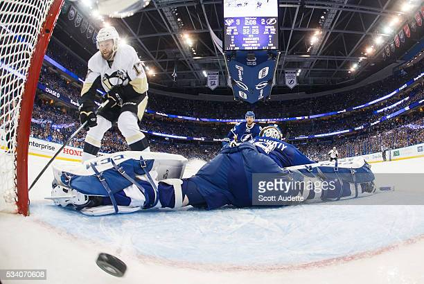 Goalie Andrei Vasilevskiy of the Tampa Bay Lightning stretches but misses the save against Bryan Rust of the Pittsburgh Penguins and lets in a goal...