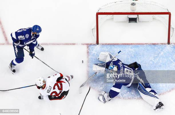 Goalie Andrei Vasilevskiy of the Tampa Bay Lightning stretches to make a save while teammate Valtteri Filppula battles against Chris Kelly of the...