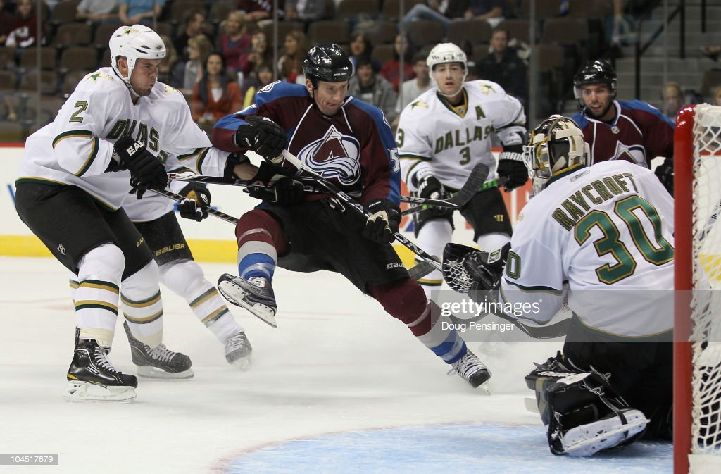Goalie Andrew Raycroft of the Dallas Star gloves the puck as Cody McLeod of the Colorado Avalanche looks for the rebound while Nicklas Grossman of...