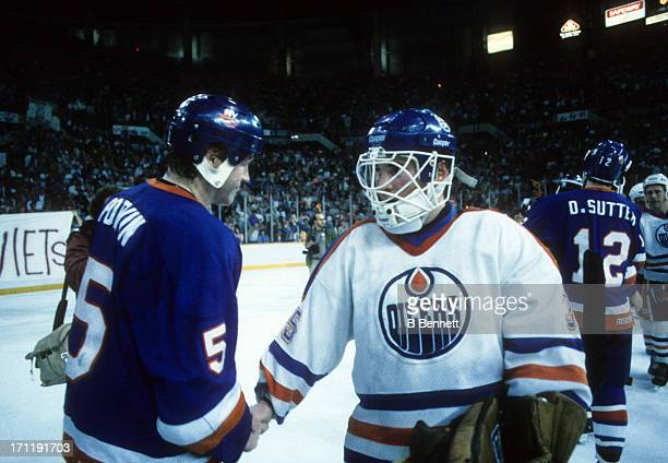 Goalie Andy Moog of the Edmonton Oilers shakes hands with Denis Potvin of the New York Islanders after Game 5 of the 1984 Stanley Cup Finals on May...