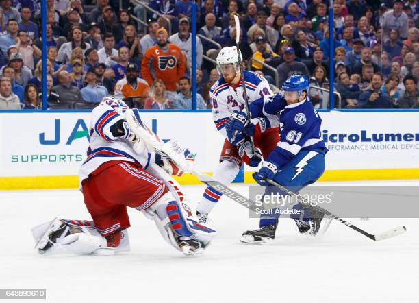 Goalie Antti Raanta of the New York Rangers clears the puck as teammate Marc Staal battles against Gabriel Dumont of the Tampa Bay Lightning during...