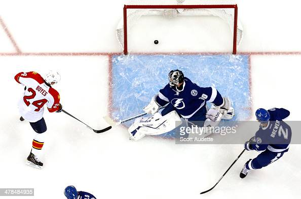 Goalie Ben Bishop and Eric Brewer of the Tampa Bay Lightning and Brad Boyes of the Florida Panthers watch the puck go into the net for a goal during...