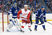 Goalie Ben Bishop and Jason Garrison of the Tampa Bay Lightning skate against Justin Abdelkader of the Detroit Red Wings during the second period of...