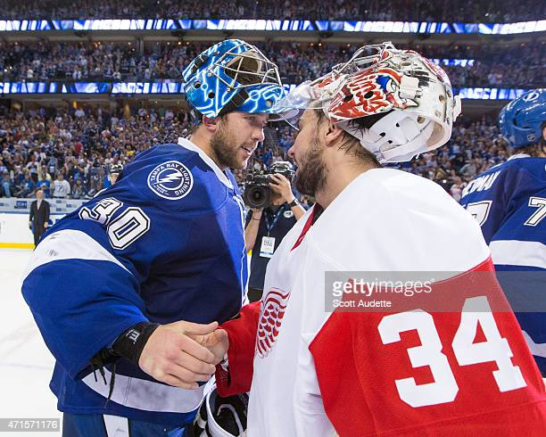 Goalie Ben Bishop of the Tampa Bay Lightning and goalie Petr Mrazek of the Detroit Red Wings shake hands after the Lightning win the series after...