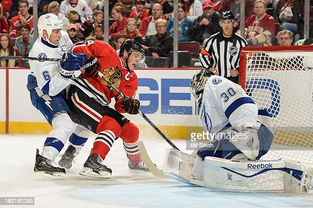 Goalie Ben Bishop of the Tampa Bay Lightning blocks the shot attempt by Jonathan Toews of the Chicago Blackhawks as Sami Salo of the Lightning pushes...