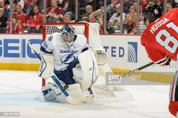 Goalie Ben Bishop of the Tampa Bay Lightning blocks the shot taken by Marian Hossa of the Chicago Blackhawks during the NHL game on October 5 2013 at...