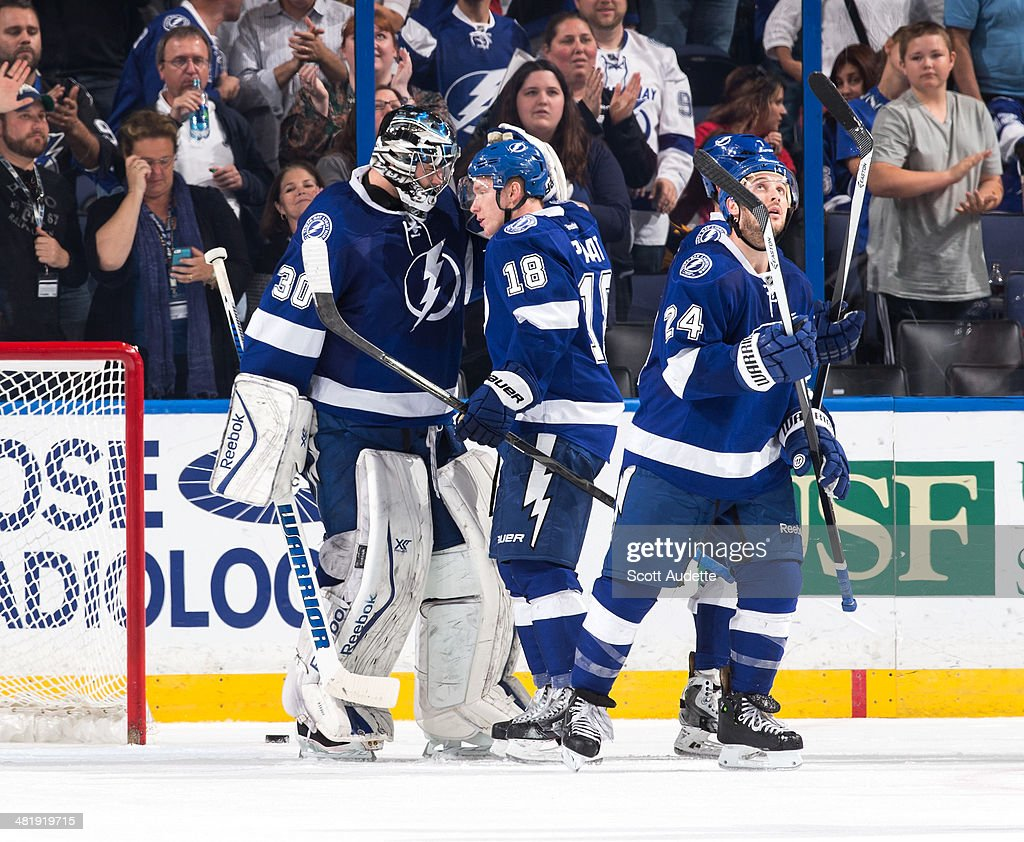 Goalie <a gi-track='captionPersonalityLinkClicked' href=/galleries/search?phrase=Ben+Bishop&family=editorial&specificpeople=700137 ng-click='$event.stopPropagation()'>Ben Bishop</a> #30 of the Tampa Bay Lightning celebrates the win with teammate Ondrej Palat #18 against the Montreal Canadiens at the Tampa Bay Times Forum on April 1, 2014 in Tampa, Florida.