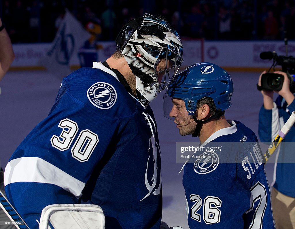 Goalie <a gi-track='captionPersonalityLinkClicked' href=/galleries/search?phrase=Ben+Bishop&family=editorial&specificpeople=700137 ng-click='$event.stopPropagation()'>Ben Bishop</a> #30 of the Tampa Bay Lightning congratulates teammate <a gi-track='captionPersonalityLinkClicked' href=/galleries/search?phrase=Martin+St.+Louis&family=editorial&specificpeople=202067 ng-click='$event.stopPropagation()'>Martin St. Louis</a> #26 on tonights win against the Minnesota Wild at the Tampa Bay Times Forum on October 17, 2013 in Tampa, Florida.