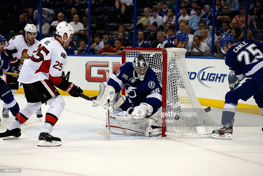 Goalie Ben Bishop #30 of the Tampa Bay Lightning eyes the puck on the net against the Ottawa Senators during the game at the Tampa Bay Times Forum on April 9, 2013 in Tampa, Florida.