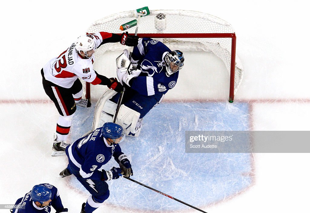 Goalie <a gi-track='captionPersonalityLinkClicked' href=/galleries/search?phrase=Ben+Bishop&family=editorial&specificpeople=700137 ng-click='$event.stopPropagation()'>Ben Bishop</a> #30 of the Tampa Bay Lightning is checked by <a gi-track='captionPersonalityLinkClicked' href=/galleries/search?phrase=Mika+Zibanejad&family=editorial&specificpeople=7832310 ng-click='$event.stopPropagation()'>Mika Zibanejad</a> #93 of the Ottawa Senators during the first period at the Tampa Bay Times Forum on December 5, 2013 in Tampa, Florida.