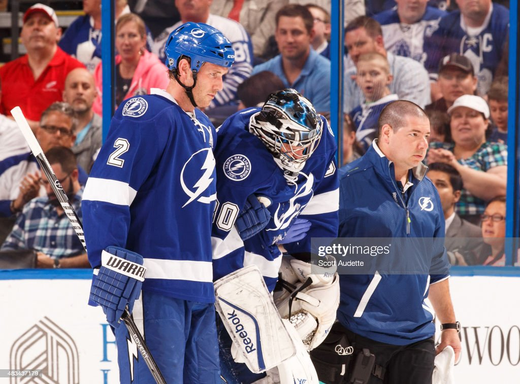 Goalie <a gi-track='captionPersonalityLinkClicked' href=/galleries/search?phrase=Ben+Bishop&family=editorial&specificpeople=700137 ng-click='$event.stopPropagation()'>Ben Bishop</a> #30 of the Tampa Bay Lightning is helped off the ice by teammate <a gi-track='captionPersonalityLinkClicked' href=/galleries/search?phrase=Eric+Brewer&family=editorial&specificpeople=202144 ng-click='$event.stopPropagation()'>Eric Brewer</a> #2 and head athletic trainer Tom Mulligan after sustaining an upper body injury during the first period against the Toronto Maple Leafs at the Tampa Bay Times Forum on April 8, 2014 in Tampa, Florida.
