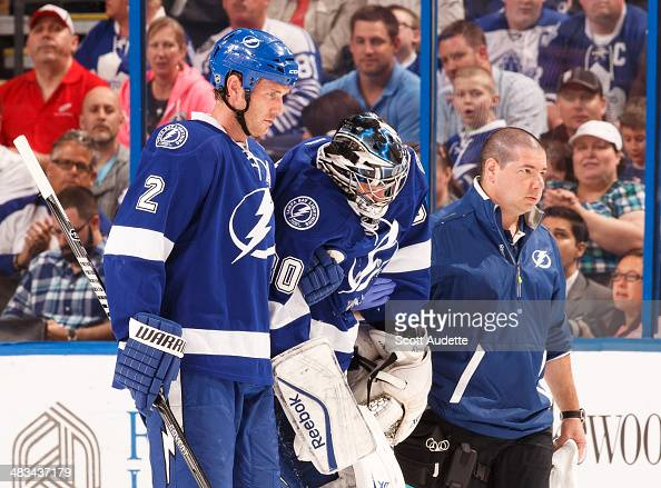 Goalie Ben Bishop of the Tampa Bay Lightning is helped off the ice by teammate Eric Brewer and head athletic trainer Tom Mulligan after sustaining an...