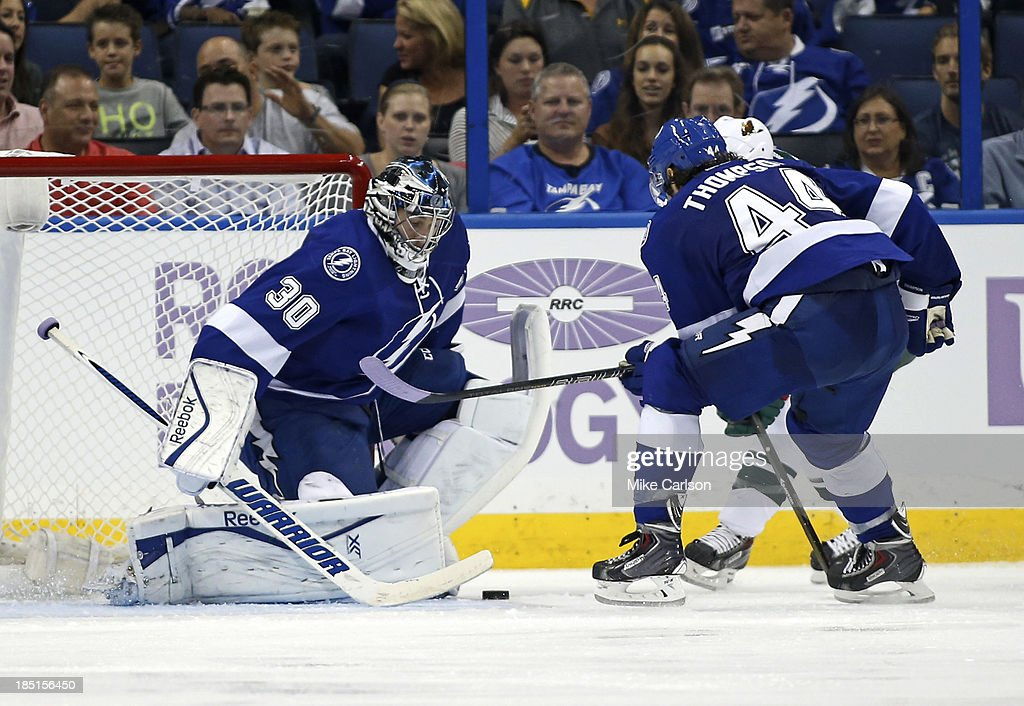 Goalie <a gi-track='captionPersonalityLinkClicked' href=/galleries/search?phrase=Ben+Bishop&family=editorial&specificpeople=700137 ng-click='$event.stopPropagation()'>Ben Bishop</a> #30 of the Tampa Bay Lightning makes a save in front of defenseman Nate Thompson #44 against the Minnesota Wild at the Tampa Bay Times Forum on October 17, 2013 in Tampa, Florida.