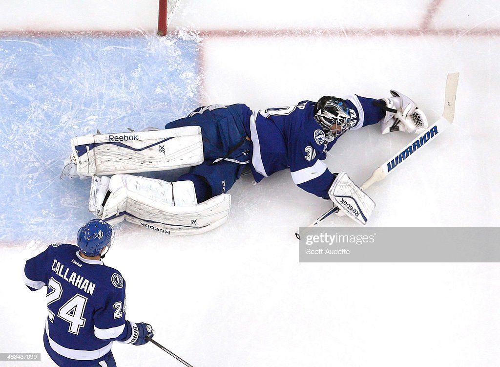 Goalie Ben Bishop #30 of the Tampa Bay Lightning makes a save while landing awkwardly and injures himself while teammate Ryan Callahan #24 looks for a rebound during the first period against the Toronto Maple Leafs at the Tampa Bay Times Forum on April 8, 2014 in Tampa, Florida.