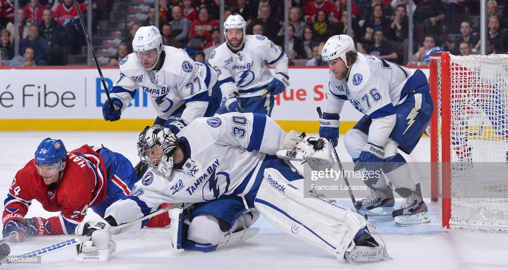 Goalie <a gi-track='captionPersonalityLinkClicked' href=/galleries/search?phrase=Ben+Bishop&family=editorial&specificpeople=700137 ng-click='$event.stopPropagation()'>Ben Bishop</a> #30 of the Tampa Bay Lightning reaches for a puck in front of the net as Pierre-Cedric Labrie #76 guards the crease in NHL action against the Montreal Canadiens on April 18, 2013 at the Bell Centre in Montreal, Quebec, Canada.