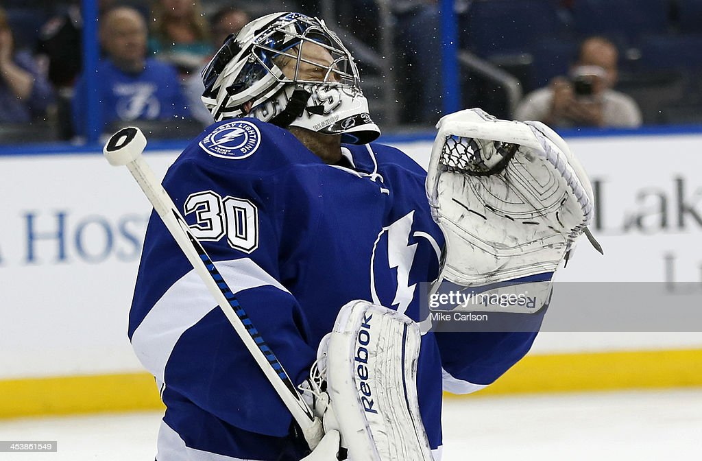 Goalie <a gi-track='captionPersonalityLinkClicked' href=/galleries/search?phrase=Ben+Bishop&family=editorial&specificpeople=700137 ng-click='$event.stopPropagation()'>Ben Bishop</a> #30 of the Tampa Bay Lightning reacts after getting hit in the mask by a shot from the Ottawa Senators at the Tampa Bay Times Forum on December 5, 2013 in Tampa, Florida.