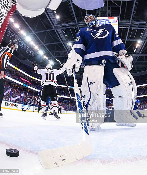Goalie Ben Bishop of the Tampa Bay Lightning reacts to a goal while Patrick Sharp of the Chicago Blackhawks celebrates during the third period in...