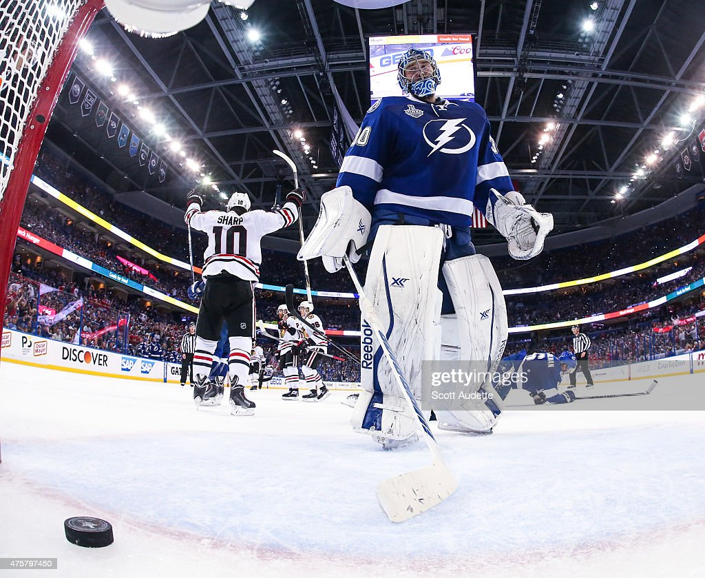 Goalie <a gi-track='captionPersonalityLinkClicked' href=/galleries/search?phrase=Ben+Bishop&family=editorial&specificpeople=700137 ng-click='$event.stopPropagation()'>Ben Bishop</a> #30 of the Tampa Bay Lightning reacts to a goal while <a gi-track='captionPersonalityLinkClicked' href=/galleries/search?phrase=Patrick+Sharp&family=editorial&specificpeople=206279 ng-click='$event.stopPropagation()'>Patrick Sharp</a> #10 of the Chicago Blackhawks celebrates during the third period in Game One of the 2015 NHL Stanley Cup Final at Amalie Arena on June 3, 2015 in Tampa, Florida.