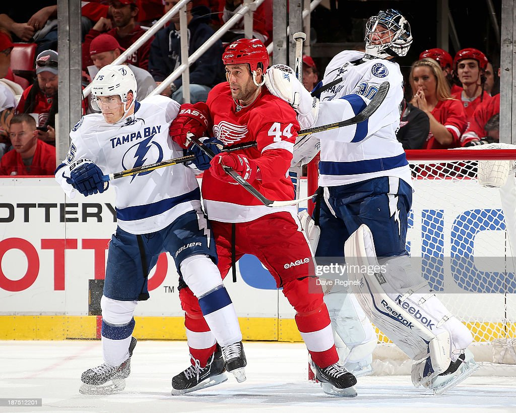 Goalie <a gi-track='captionPersonalityLinkClicked' href=/galleries/search?phrase=Ben+Bishop&family=editorial&specificpeople=700137 ng-click='$event.stopPropagation()'>Ben Bishop</a> #30 of the Tampa Bay Lightning stands on the tip of his blades to see over teammate <a gi-track='captionPersonalityLinkClicked' href=/galleries/search?phrase=Matt+Carle&family=editorial&specificpeople=582495 ng-click='$event.stopPropagation()'>Matt Carle</a> #25 and <a gi-track='captionPersonalityLinkClicked' href=/galleries/search?phrase=Todd+Bertuzzi&family=editorial&specificpeople=202476 ng-click='$event.stopPropagation()'>Todd Bertuzzi</a> #44 of the Detroit Red Wings in front of the net during an NHL game at Joe Louis Arena on November 9, 2013 in Detroit, Michigan. Tampa Bay defeated Detroit 3-2 in OT