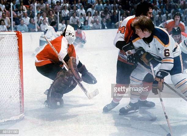 Goalie Bernie Parent of the Philadelphia Flyers waits for the shot as teammate Joe Watson defends against Jim Schoenfeld of the Buffalo Sabres during...