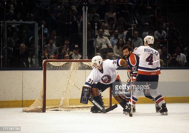 Goalie Billy Smith and Paul Boutilier of the New York Islanders defend the net against Dave Semenko of the Edmonton Oilers during the 1984 Stanley...