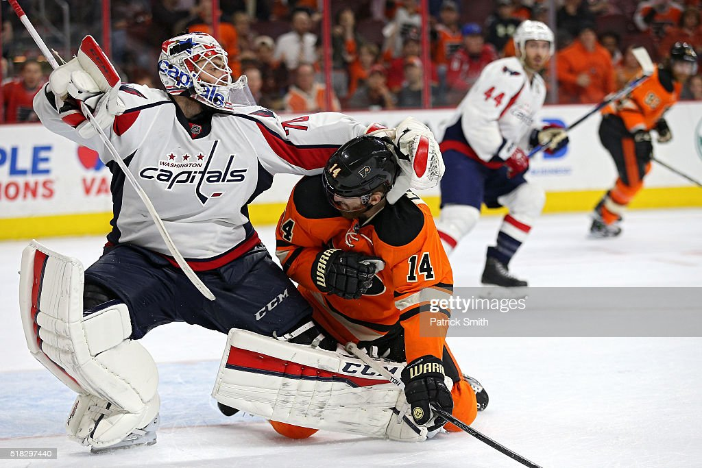 Goalie Braden Holtby #70 of the Washington Capitals and Sean Couturier #14 of the Philadelphia Flyers push and shove one another during overtime at Wells Fargo Center on March 30, 2016 in Philadelphia, Pennsylvania. The Philadelphia Flyers won in a shootout.