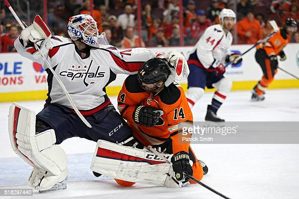 Goalie Braden Holtby of the Washington Capitals and Sean Couturier of the Philadelphia Flyers push and shove one another during overtime at Wells...