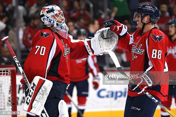 Goalie Braden Holtby of the Washington Capitals celebrates with teammate Nate Schmidt after defeating the Columbus Blue Jackets at Verizon Center on...
