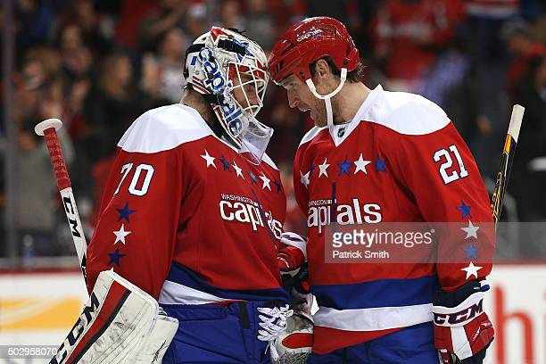 Goalie Braden Holtby of the Washington Capitals celebrates with teammate Brooks Laich after defeating the Buffalo Sabres at Verizon Center on...