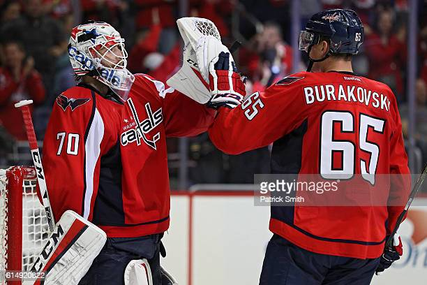 Goalie Braden Holtby of the Washington Capitals celebrates with teammate Andre Burakovsky after defeating the New York Islanders at Verizon Center on...